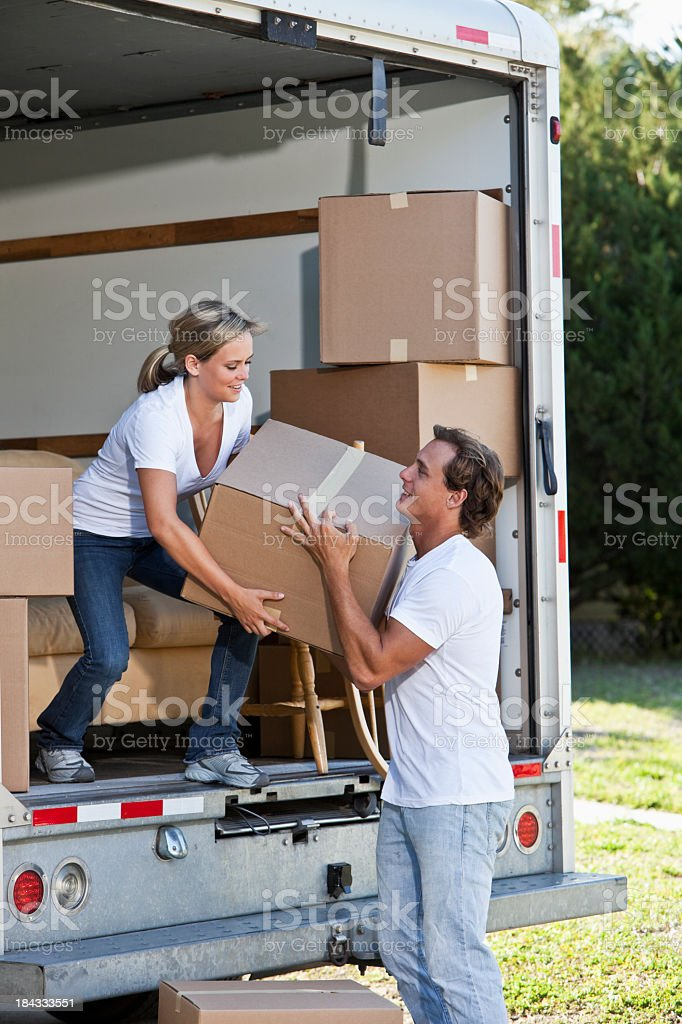 Young couple with moving van in driveway lifting boxes stock photo