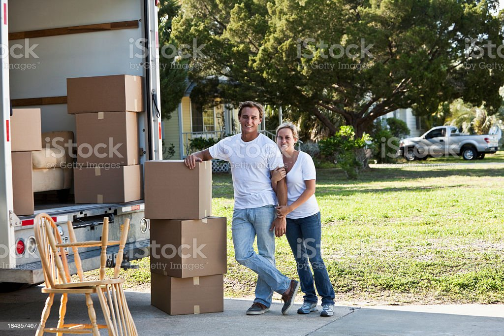 Young couple with moving van in driveway stock photo