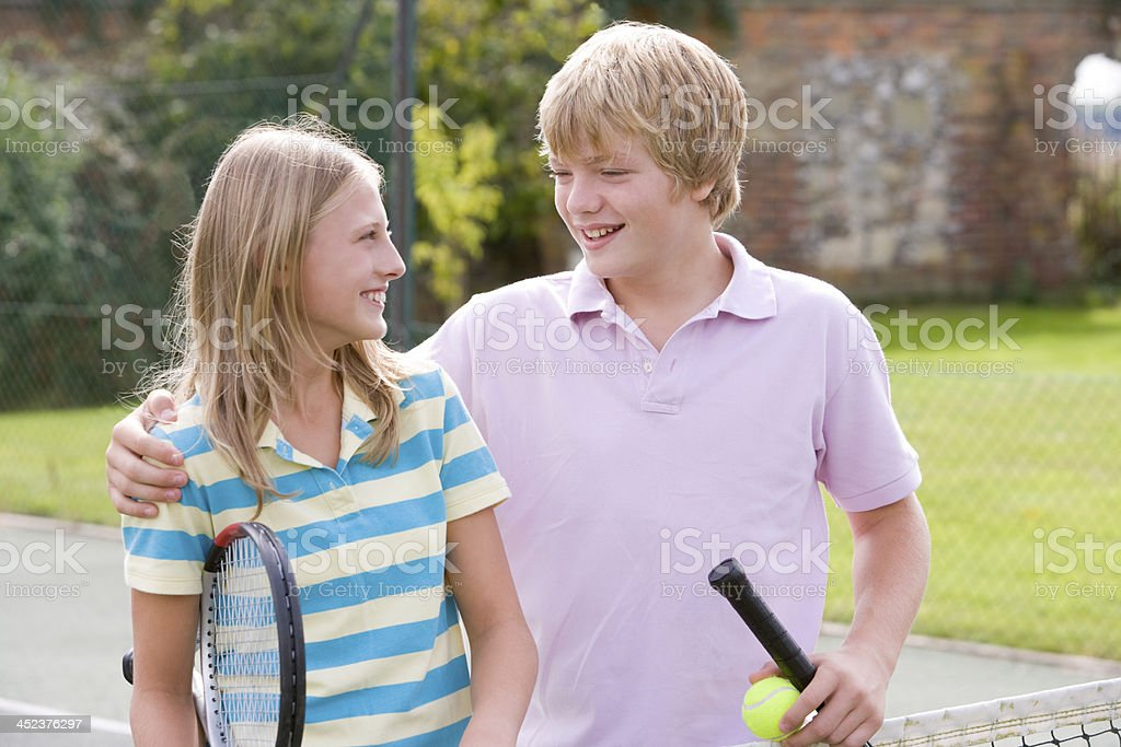 Young couple with rackets on tennis court smiling royalty-free stock photo