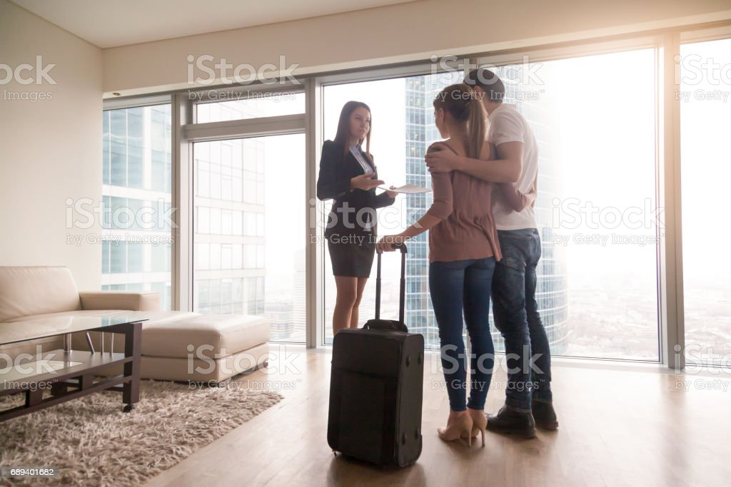 Young couple with suitcase meeting with female realtor, renting apartment stock photo