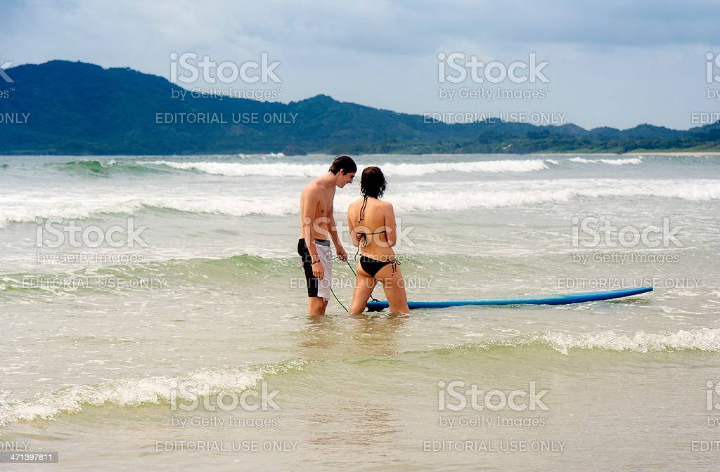 Young couple with surfboard on Tamarindo Beach in Costa Rica royalty-free stock photo