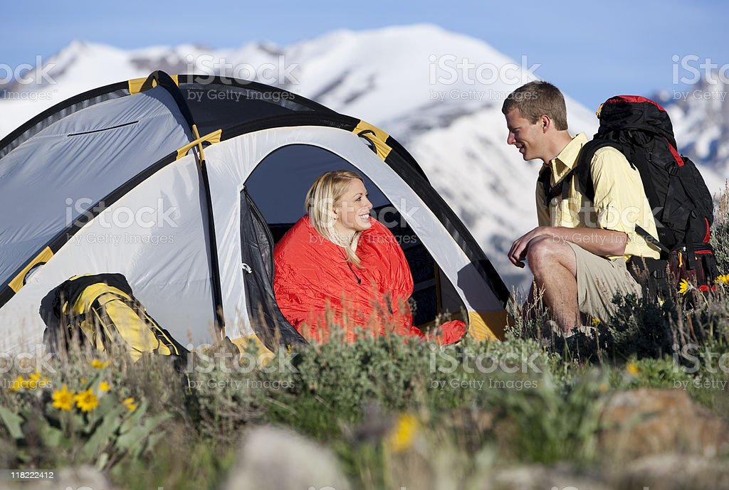 Young Couple With Tent and Backpack Hiking In The Mountains royalty-free stock photo
