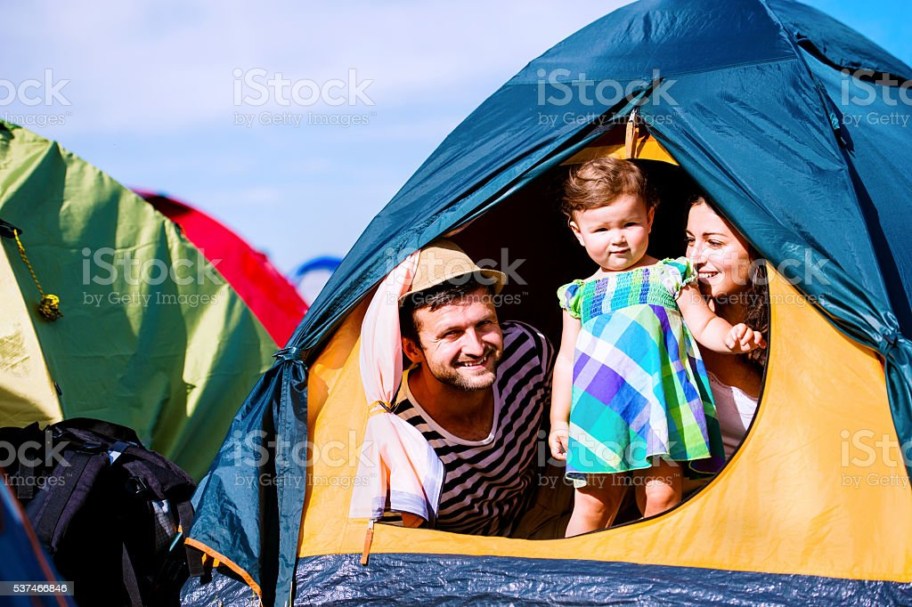 Young couple with their baby daughter in tent, summer stock photo