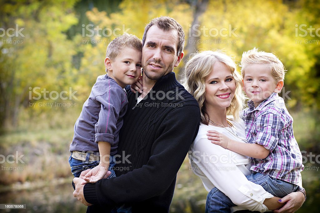 Young couple with two sons with autumnal background royalty-free stock photo