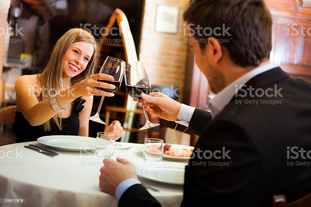 Young couple with wine glasses having dinner in restaurant royalty-free stock photo