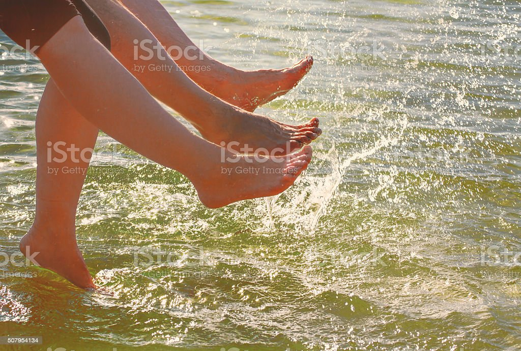 Young couplel talking feet in the water. stock photo