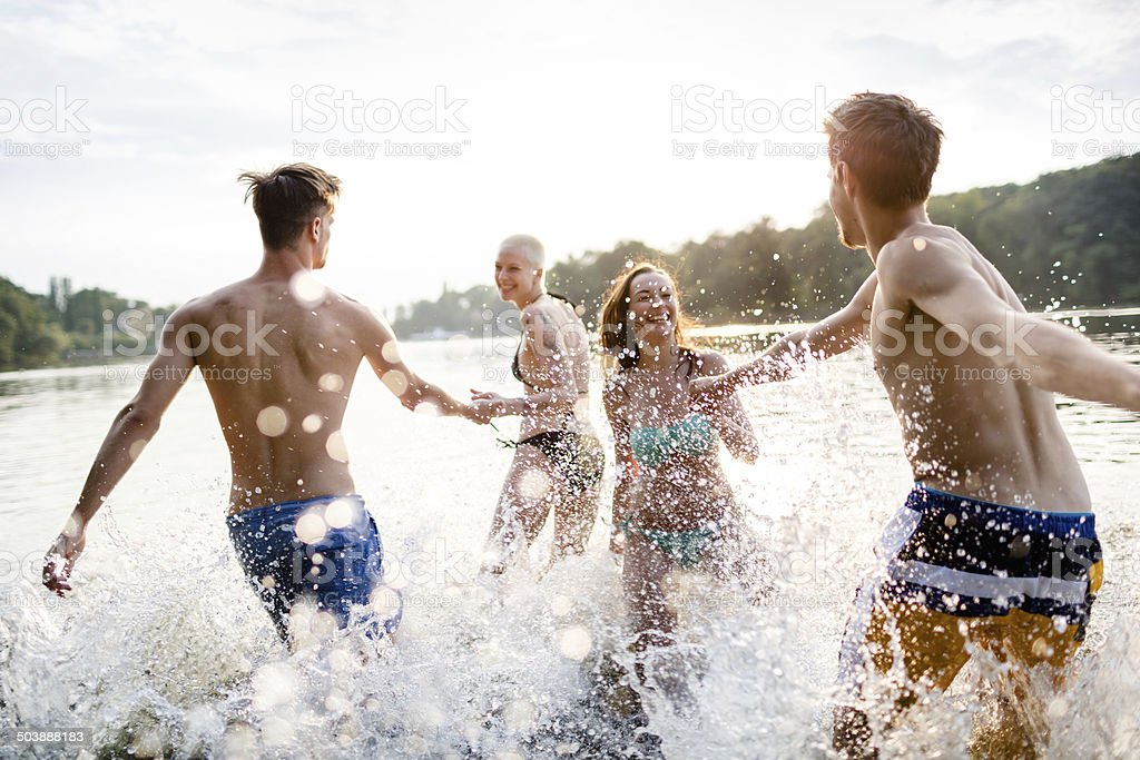 Young Couples Running In Lake stock photo