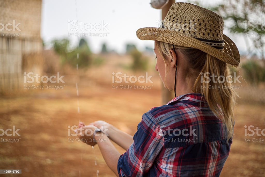 Young cow girl in farm land-Raining stock photo