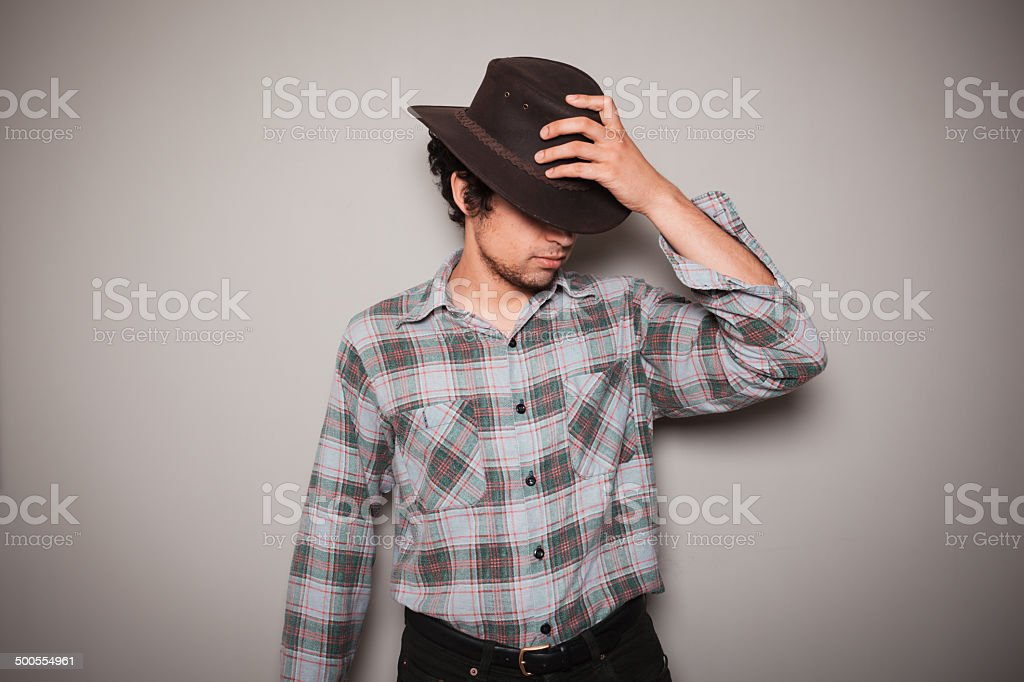 Young cowboy in plaid shirt against a green wall stock photo