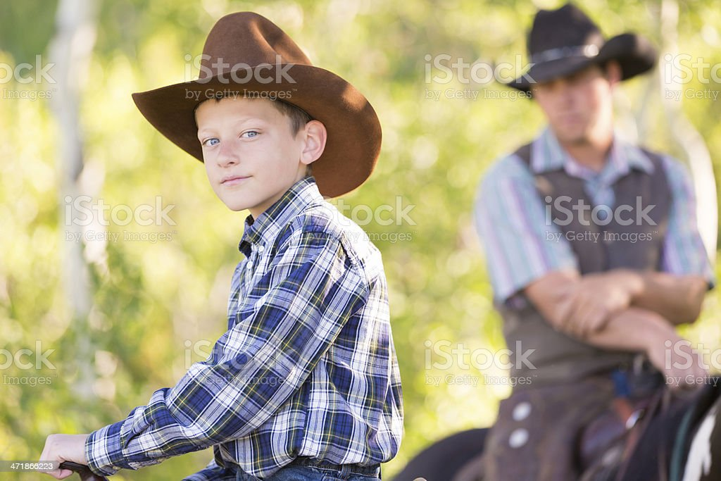 Young cowboy riding horses with father at ranch royalty-free stock photo