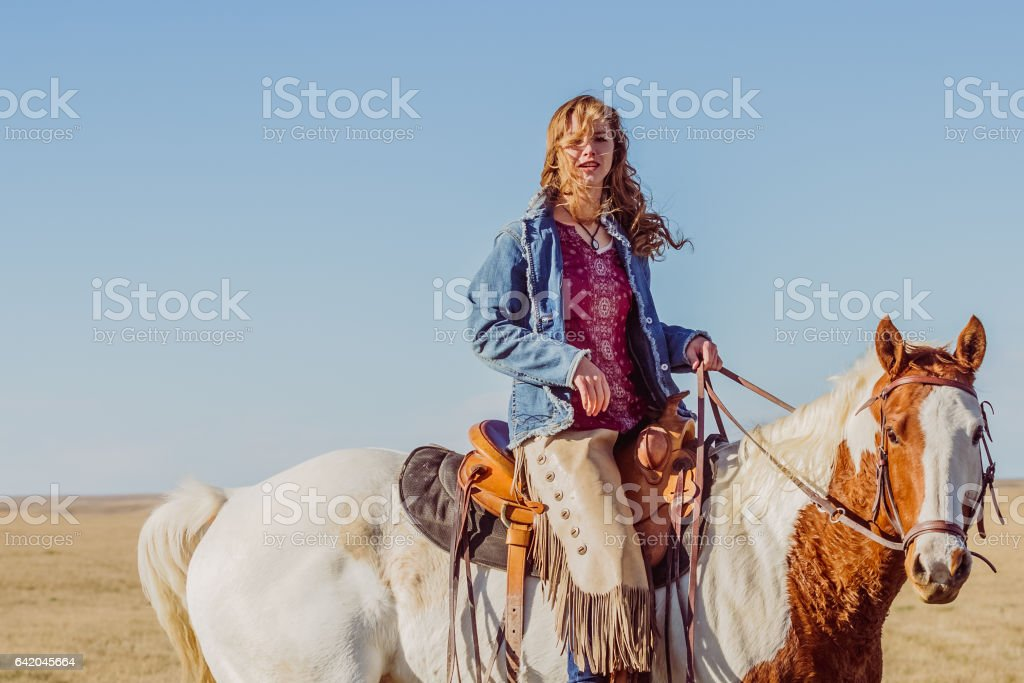 Young Cowgirl Riding Horseback stock photo