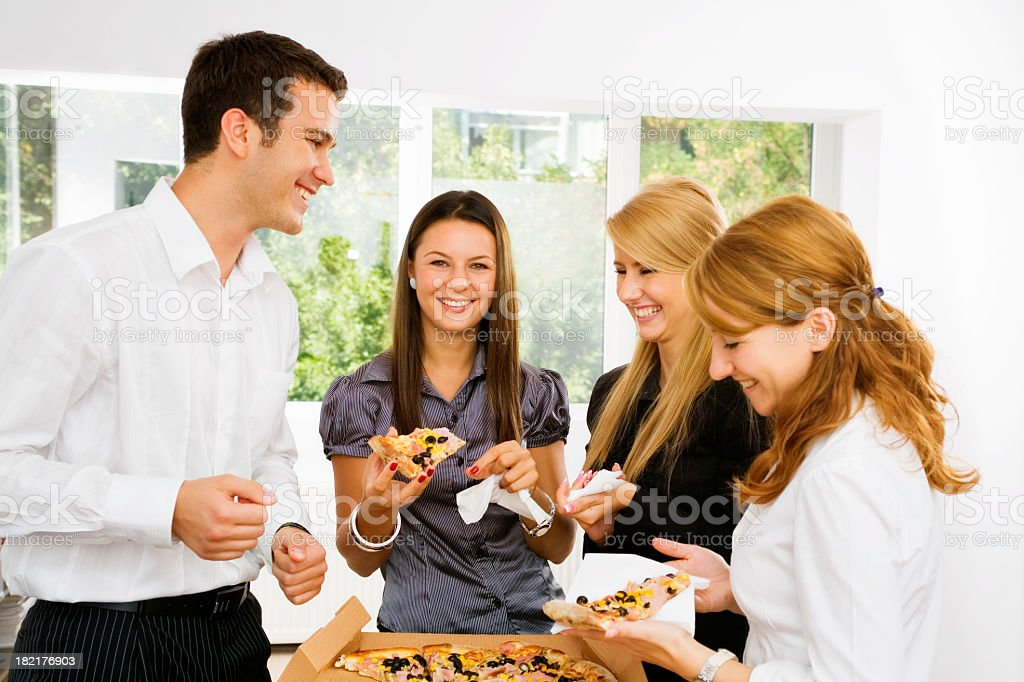 Young coworkers sharing a pizza at lunch break royalty-free stock photo