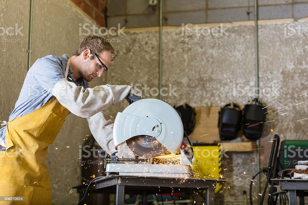 Young craftsman working with saw in professional metal shop stock photo