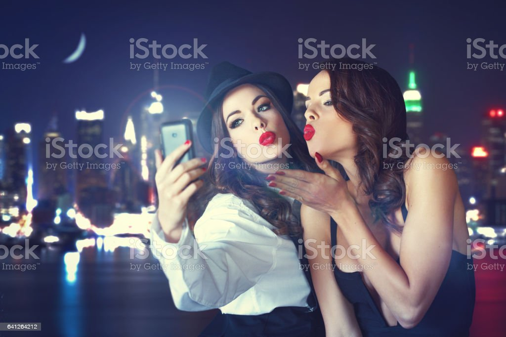 Young crazy girlfriends taking selfie at night in city stock photo