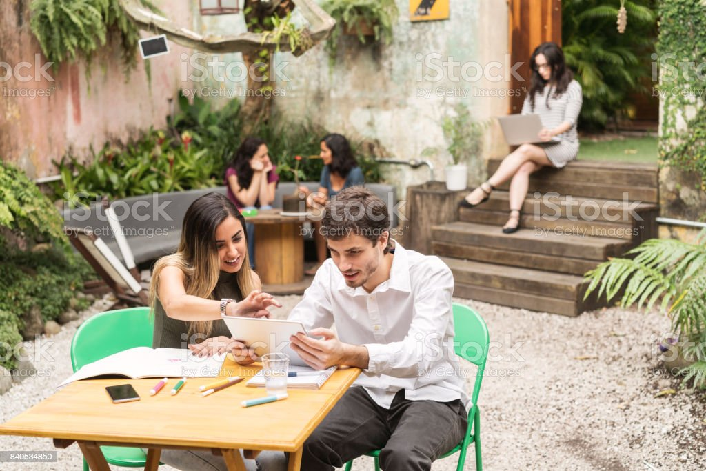 Young creative business people using digital tablet while working outside office stock photo