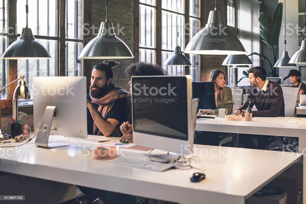 Young creative business people working late in the office stock photo