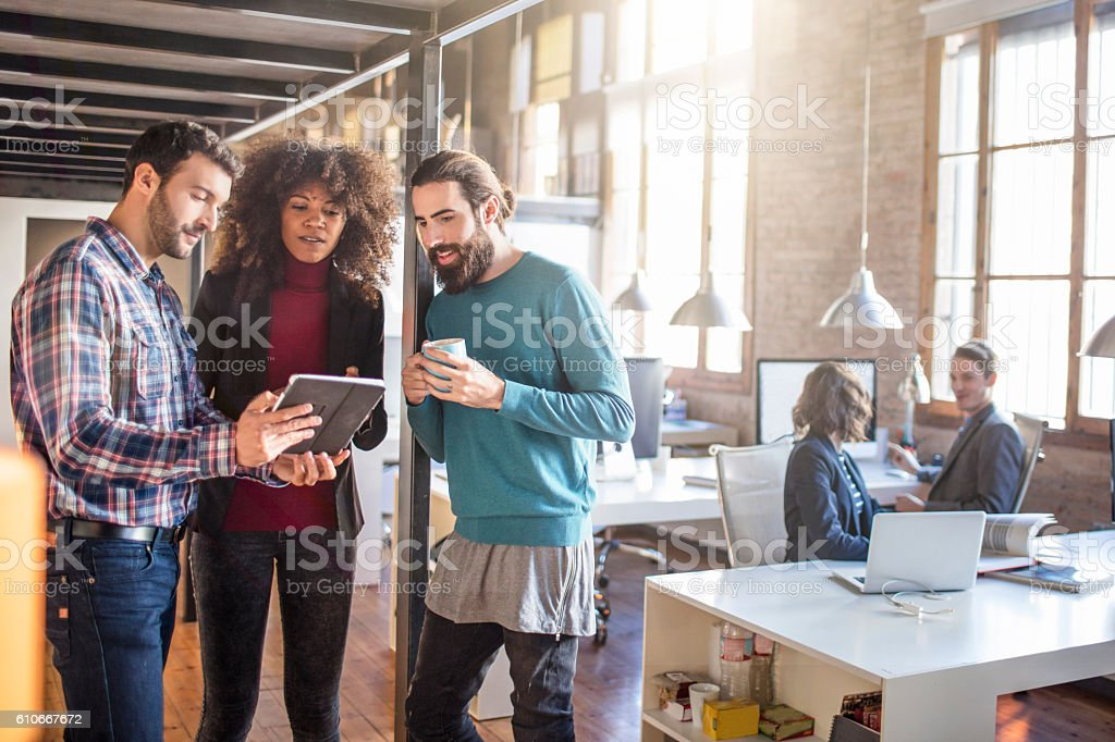 Young creative business reviewing some work in the digital tablet stock photo