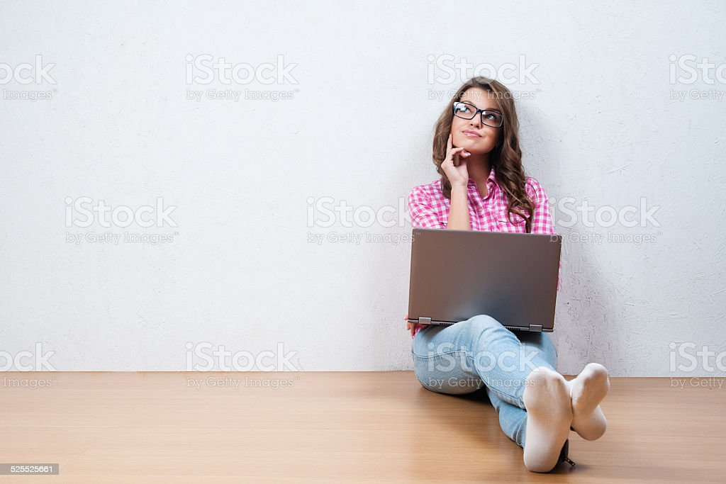 Young creative woman sitting in the floor with laptop. stock photo