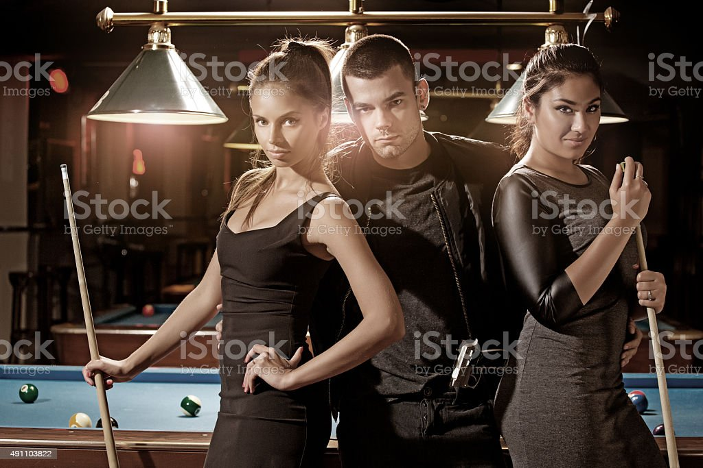 young criminal at pool hall with two women stock photo