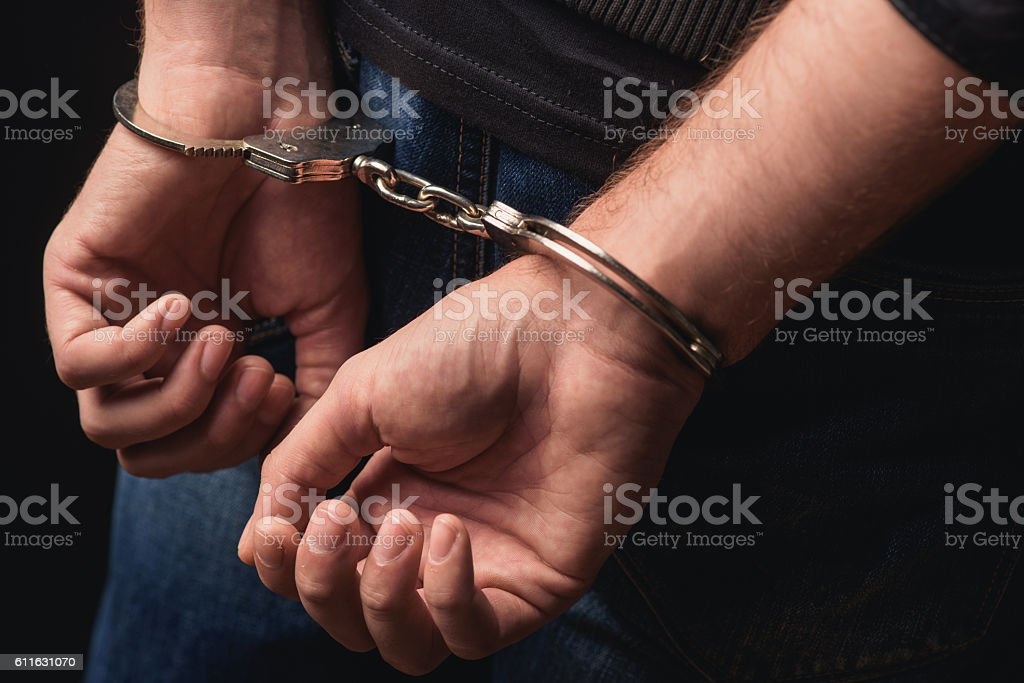 Young criminal standing in handcuffs stock photo