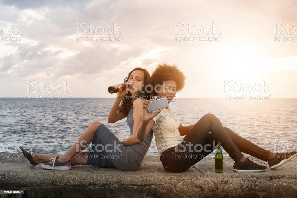 Young Cuban Friends Sit by the Seaside, Malecon, Havana, Cuba stock photo