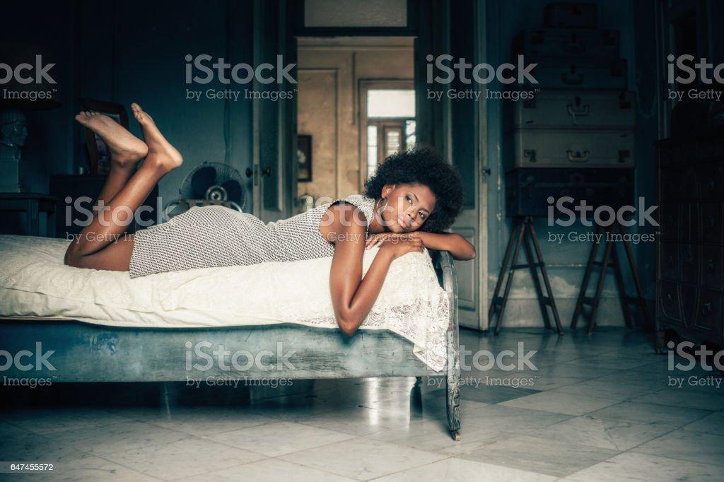 Young Cuban woman lying on bed, Havana, Cuba stock photo