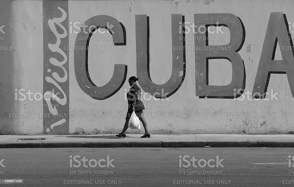Young Cuban woman passing a wall in old Havana Cuba. stock photo