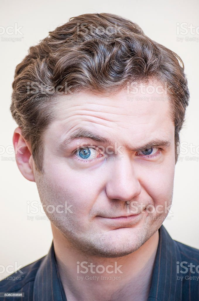 Young, curly man questionably, mistrustfully looking with raised eyebrow stock photo