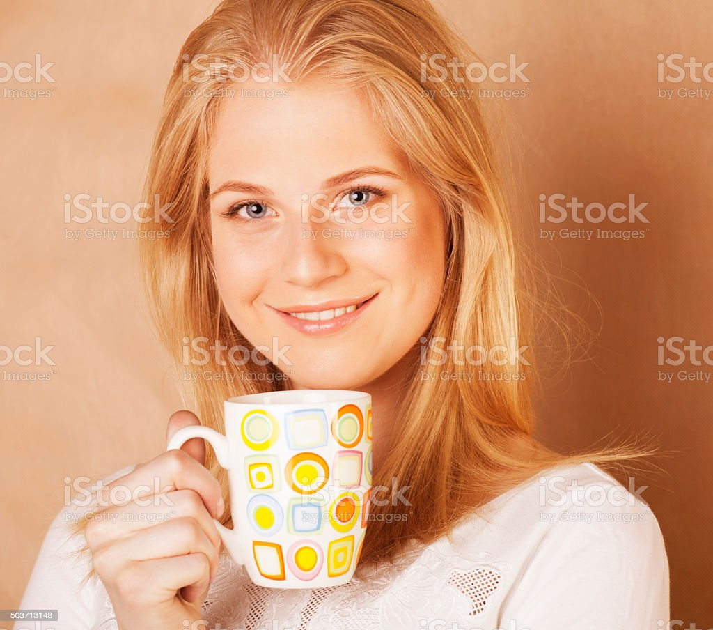 young cute blond girl drinking coffee close up on warm stock photo