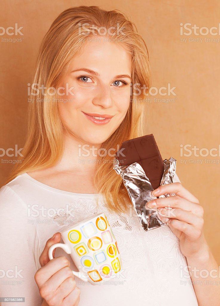 young cute blond girl eating chocolate and drinking coffee close stock photo