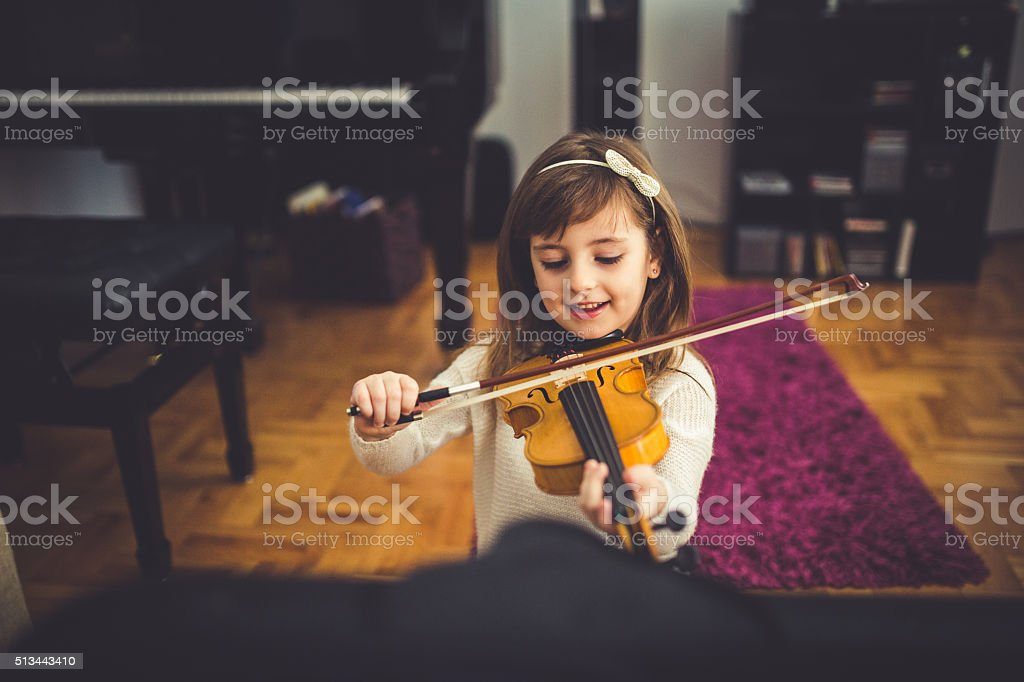Young cute girl playing violin at home stock photo