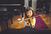 Young cute girl playing violin at home