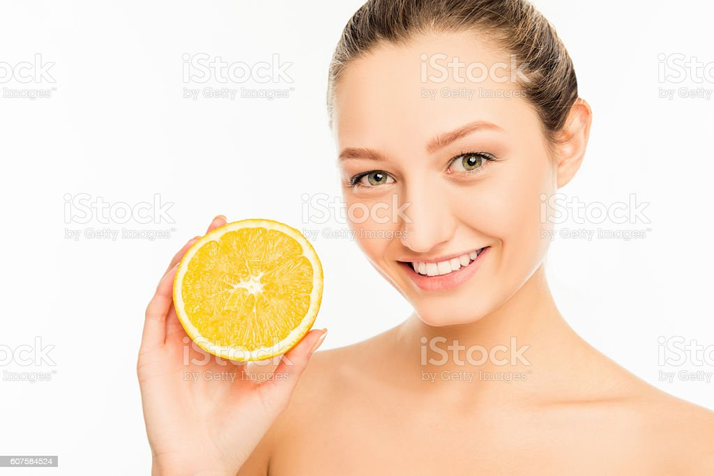 Young cute girl with nice smile and orange slice stock photo