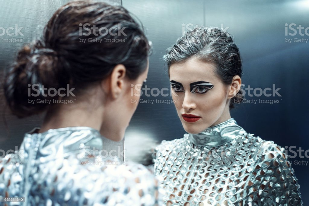 Young cyber woman in silver futuristic costume looking in the mirror. stock photo