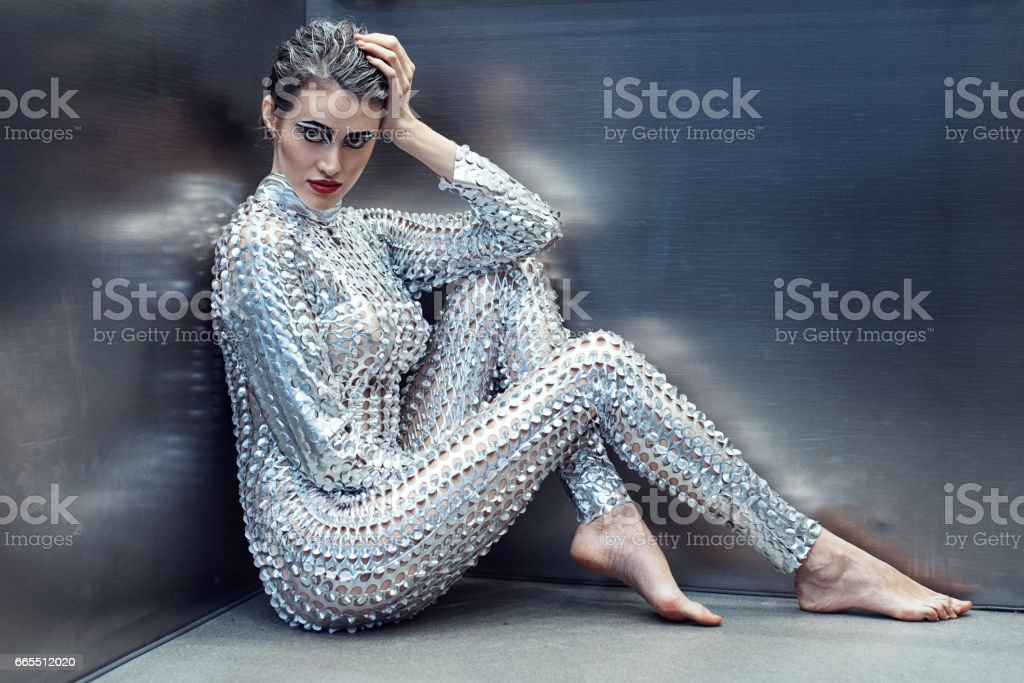 Young cyber woman in silver futuristic costume sitting in the elevator. stock photo