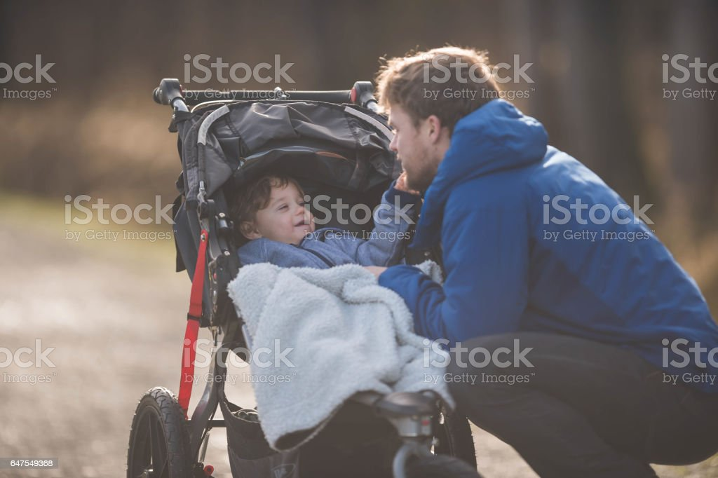 Young dad with boy in stroller stock photo