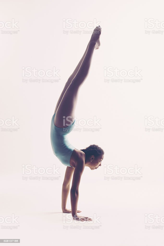 Young dancer dancer standing on hands stock photo