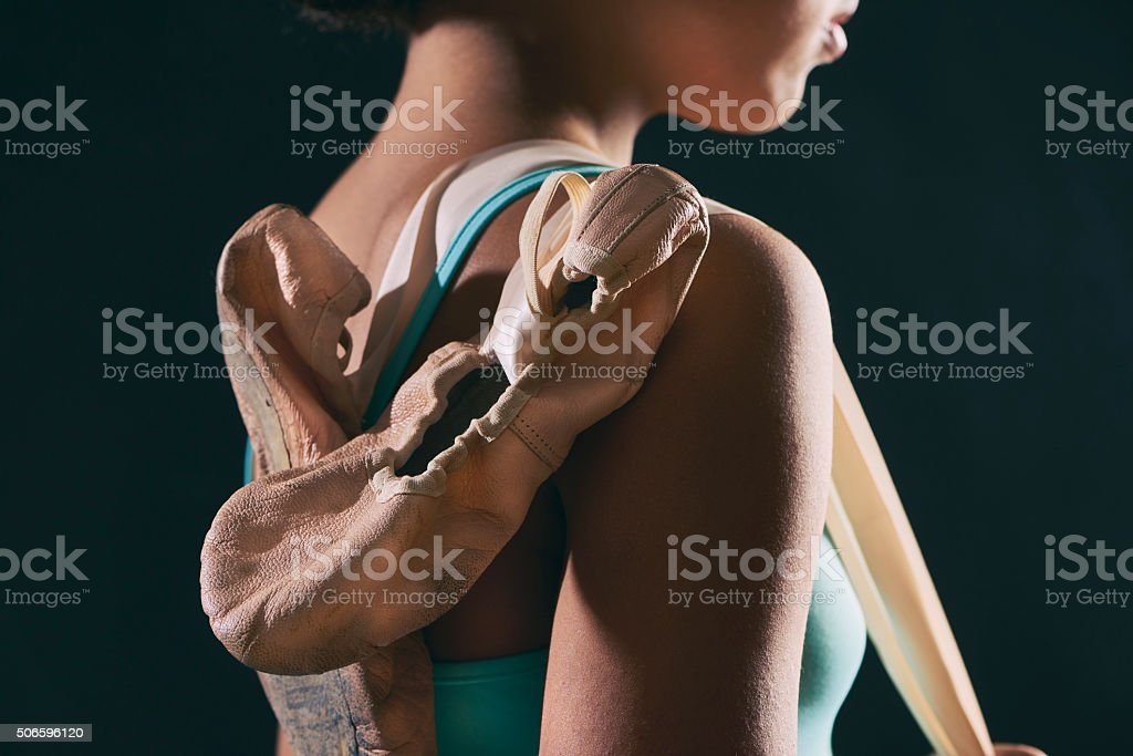 Young dancer in turqoise clothes holding her shoes stock photo