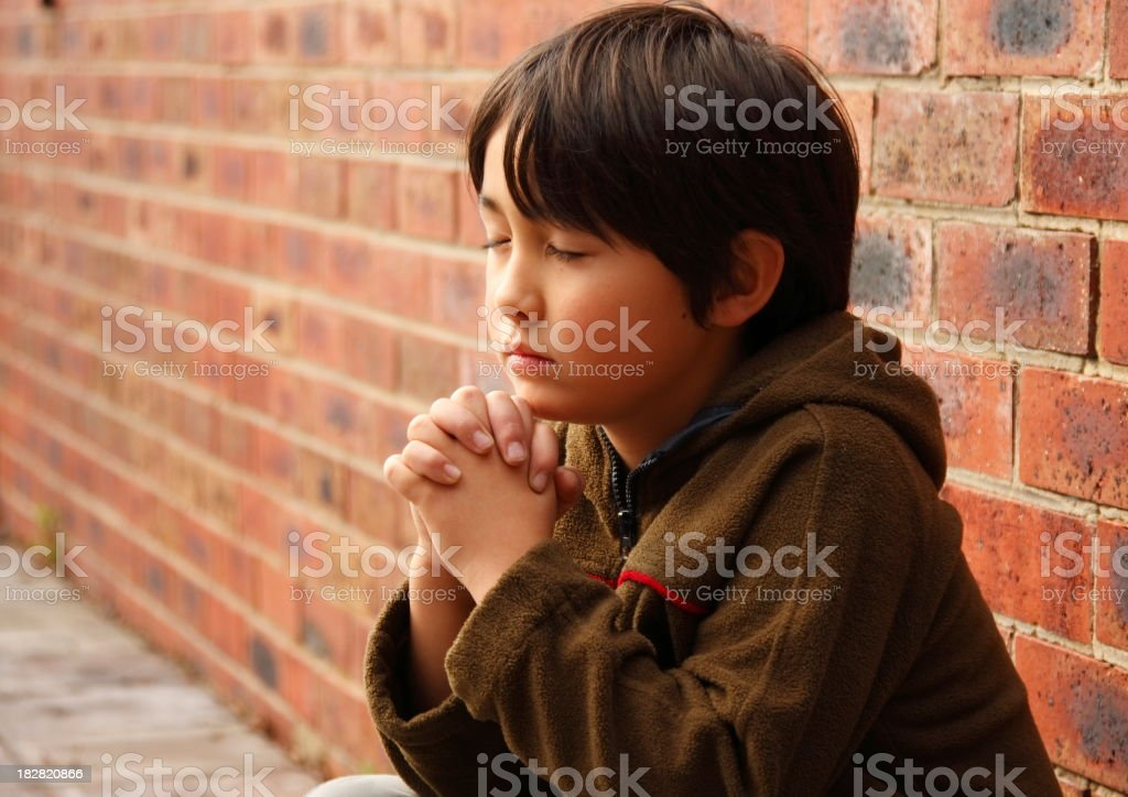 Young dark haired child praying next to a wall stock photo