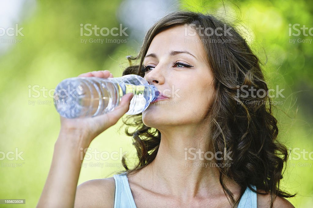 young dark-haired woman drinking water stock photo