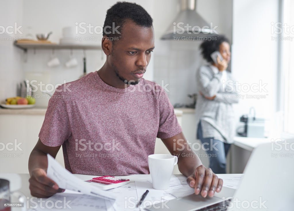 Young dark-skinned male managing family budget at home, paying gas...