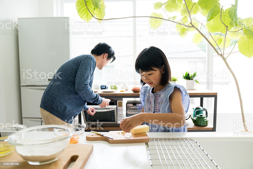 Young daughter baking with father stock photo