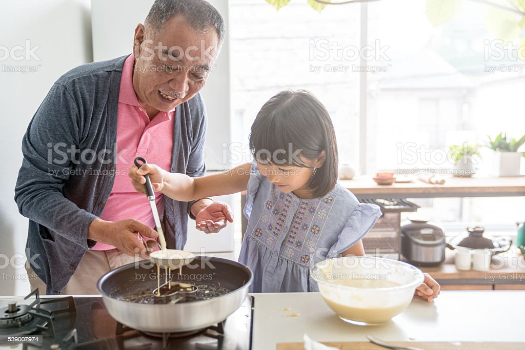 Young daughter baking with grandfather stock photo