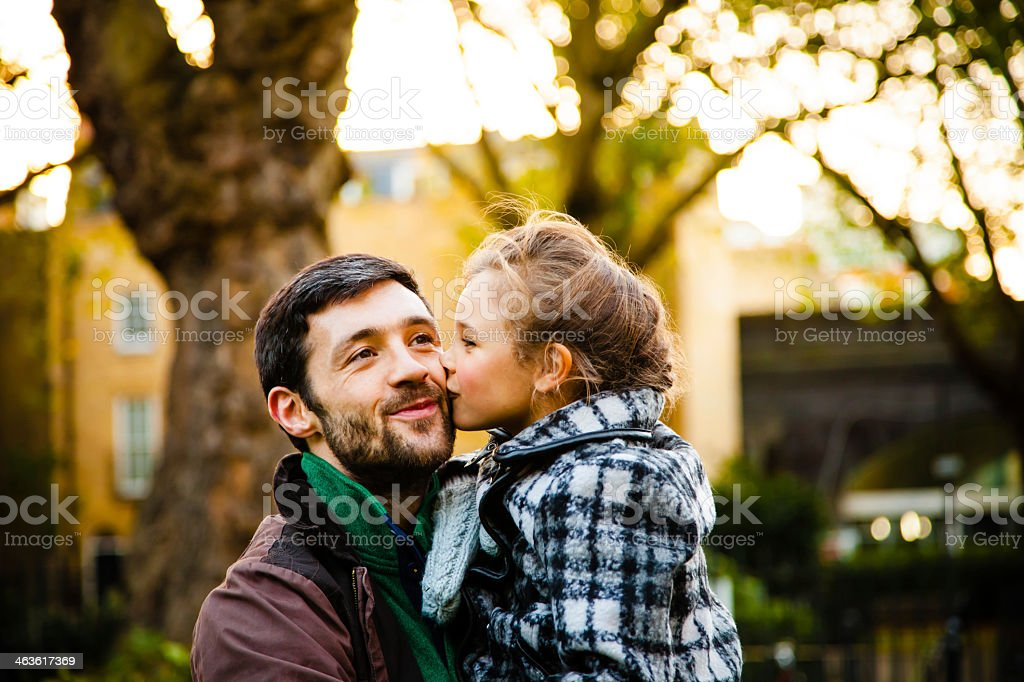 Young daughter kissing fathers cheek while he carries her stock photo