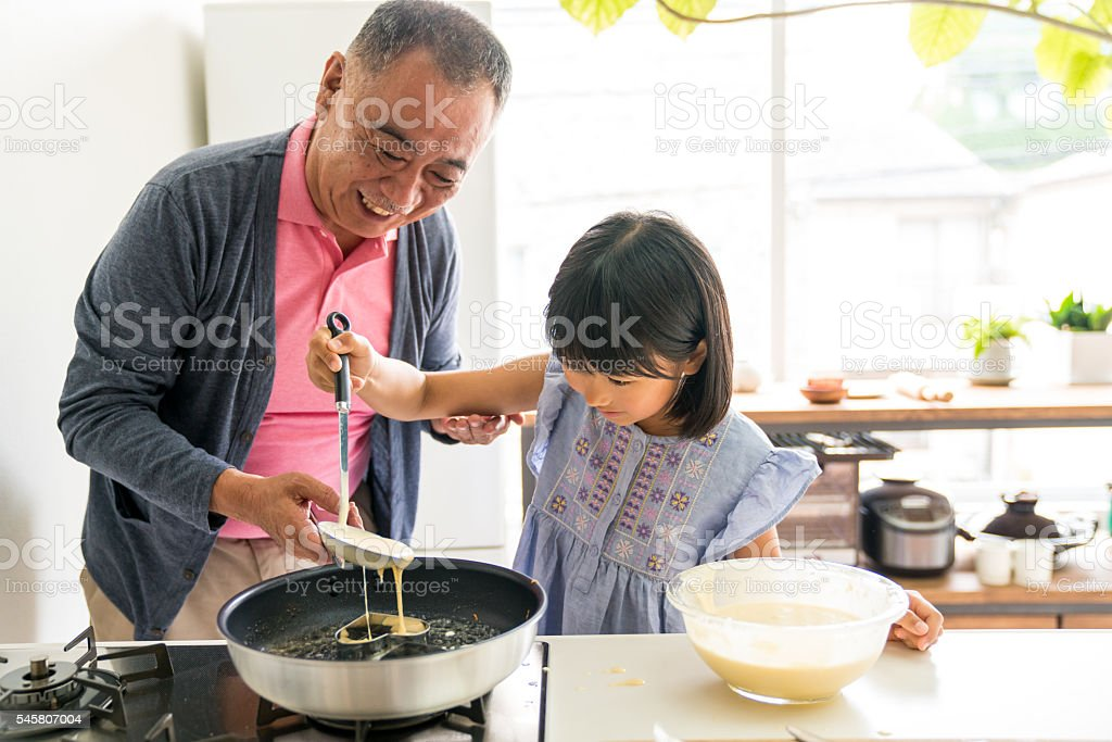 Young daughter making a cake with grandfather stock photo