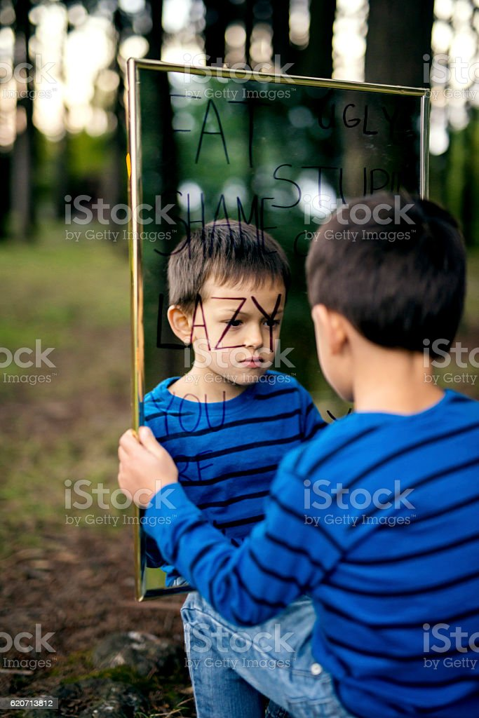 Young depressed boy looking at himself in mirror of lies stock photo