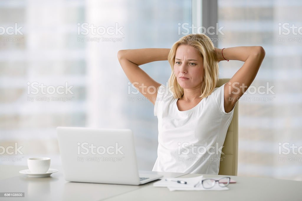 Young depressed woman at laptop stock photo