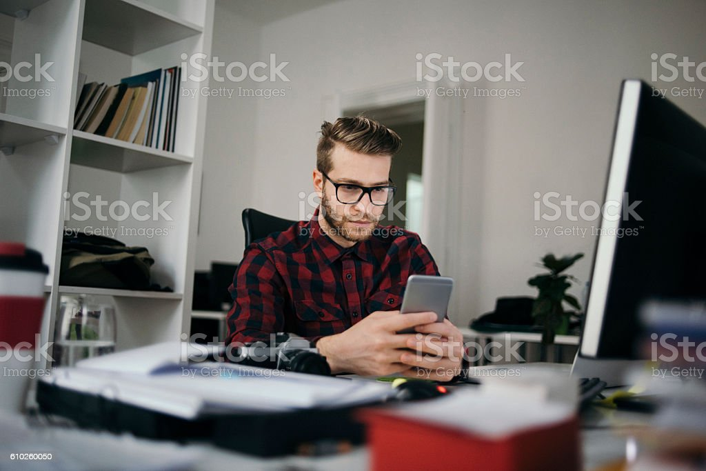 Young designer checking his email over the phone stock photo