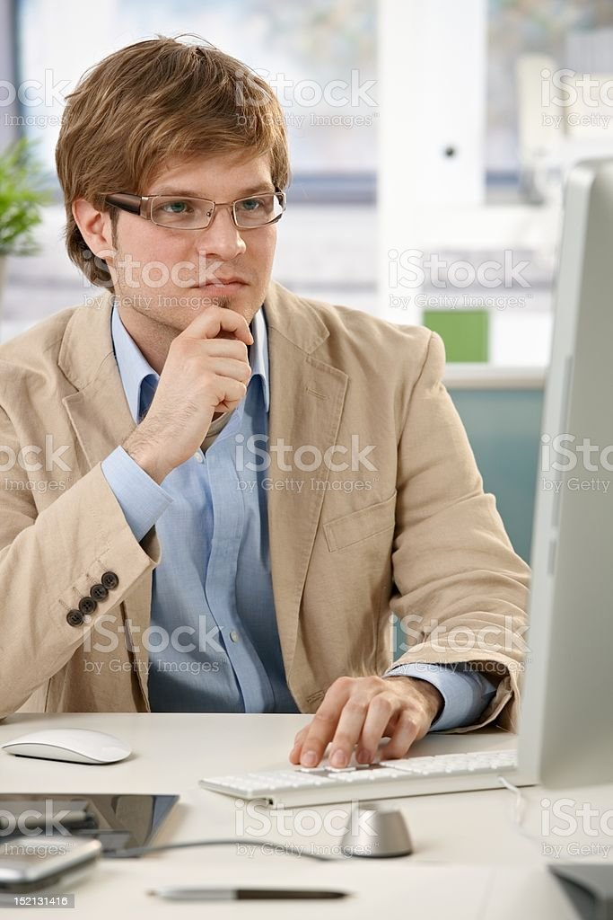 Young designer thinking at desk royalty-free stock photo