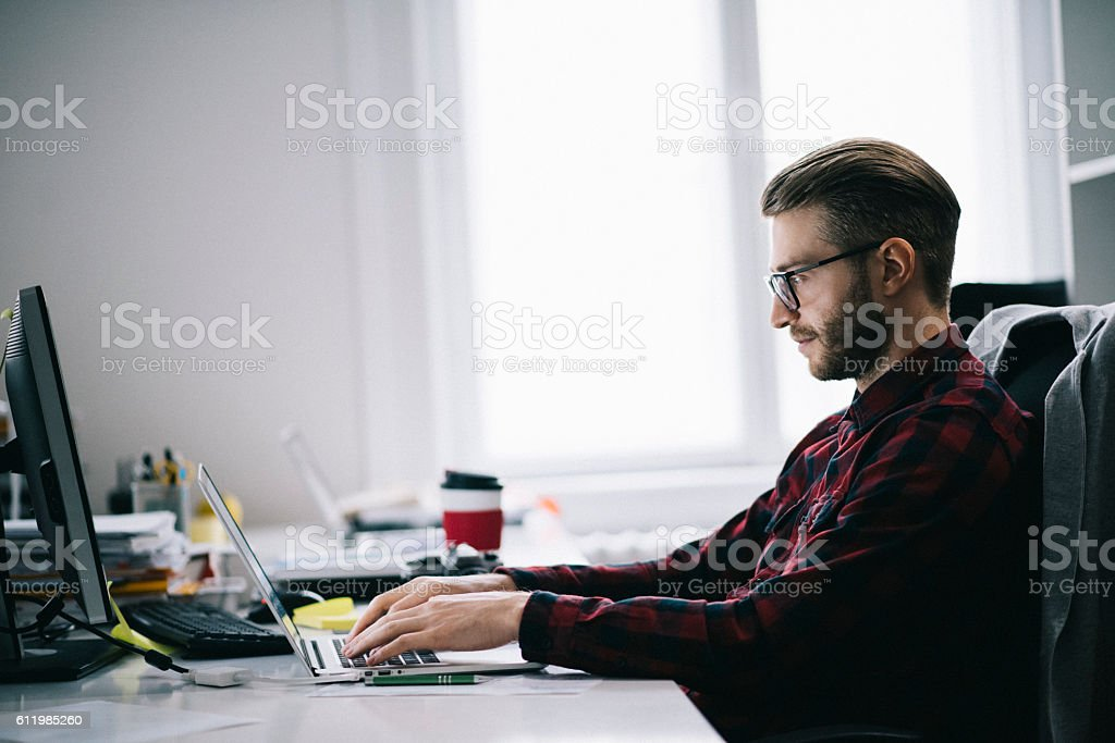 Young designer working in his office stock photo